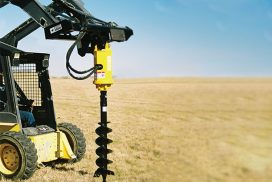 Heavy duty auger attached to skid steer